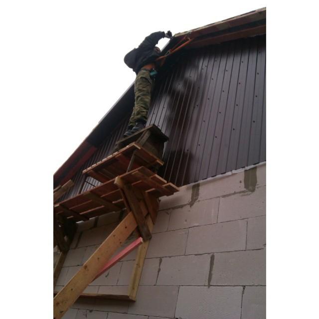 Мужчина выполняет монтаж фронтона из профнастила